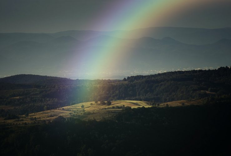 Rainbow over landscape with meadow
